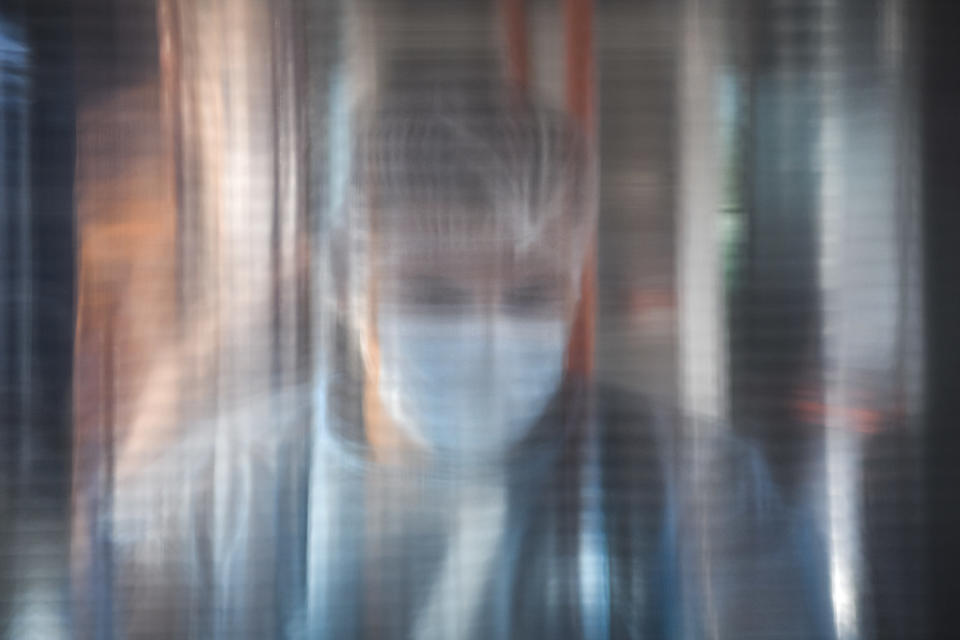 A medical worker is seen through a plastic panel in a bus that will serve as a mobile COVID-19 vaccination unit in Bucharest, Romania, Saturday, Sept. 4, 2021. The inhabitants of Romania's capital will be able to get a Johnson&Johnson COVID-19 vaccine without an appointment in the latest attempt by Romanian authorities to increase vaccination rates as the number of infections is on a constant rise in the country. (AP Photo/Andreea Alexandru)