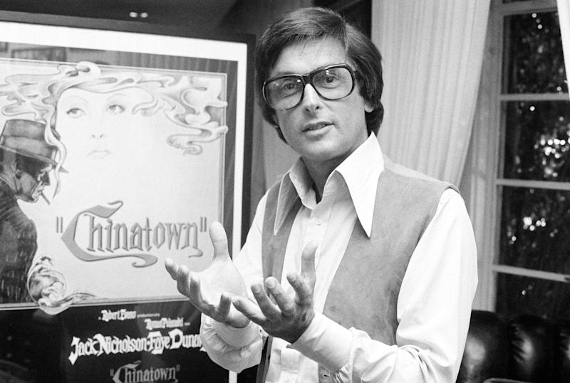 """Paramount Pictures production chief Robert Evans talks about his film """"Chinatown"""" in his Beverly Hills office in December, 1974. The poster, seen here in the background, depicts stars Jack Nicholson and Faye Dunaway in a wreath of smoke. """"We needed a more commercial approach to hit the drive-in-crowd,"""" said another Paramount executive in explaining why the poster sprouted a gun after the first release of the movie. (AP Photo/Jeff Robbins)"""