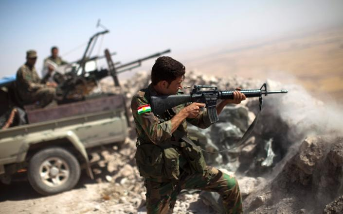 An Iraqi Kurdish Peshmerga fighter fires at Islamic-State militant positions, from his position on the top of Mount Zardak on September 9, 2014 (AFP Photo/JM Lopez)