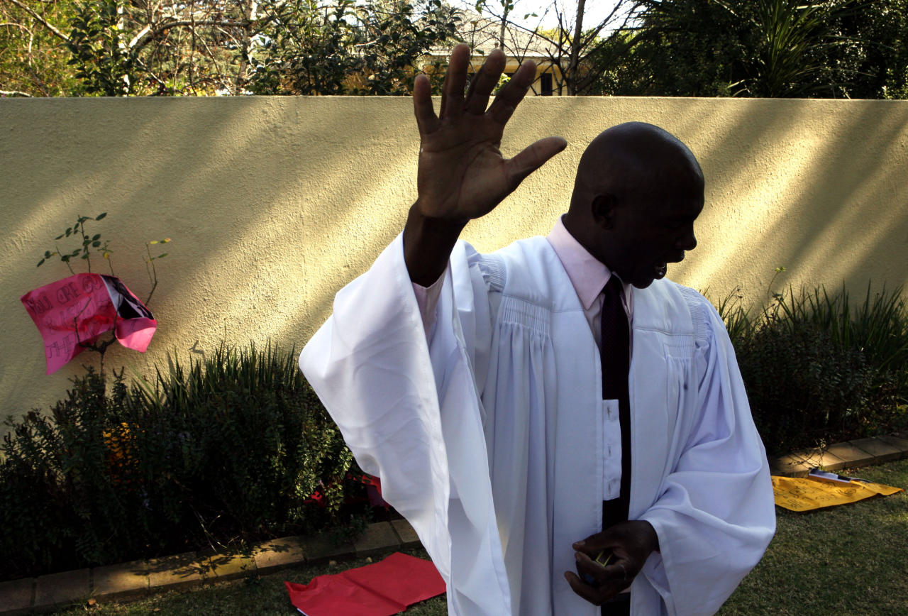Unidentified representative of a church prays for the health of former President Mandela outside his home in Johannesburg, South Africa, Sunday, June 16, 2013. The 94-year-old Mandela remains in the hospital for an eighth day, after being hospitalized for a recurring lung infection. (AP Photo/Themba Hadebe)