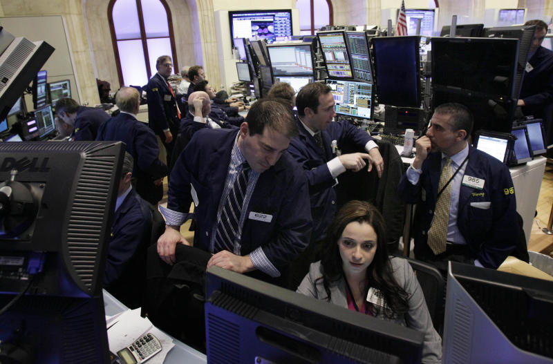 Traders work in their booth on the floor of the New York Stock Exchange Tuesday, Feb. 28, 2012. The Dow Jones industrial average closed above 13,000 Tuesday, the first time since May 2008, four months before the financial crisis. (AP Photo/Richard Drew)