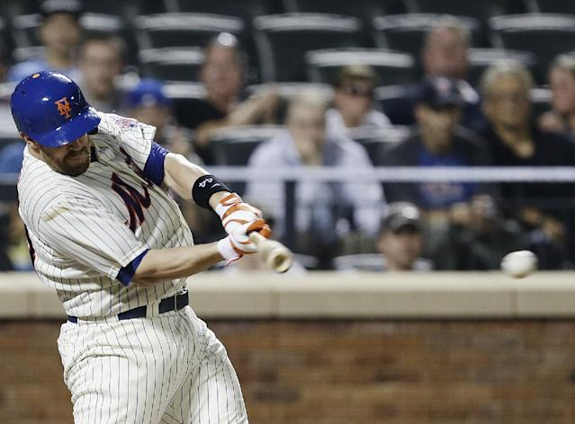 New York Mets' John Buck hits an RBI single during the sixth inning of a baseball game against the Atlanta Braves Tuesday, July 23, 2013, in New York. (AP Photo/Frank Franklin II)