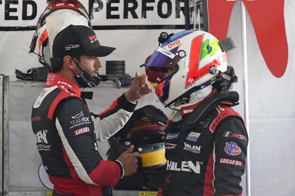 Felipe Nasr, left, and Pipo Derani, both from Brazil, talk in their pit stall during a practice session for the Rolex 24 hour race at Daytona International Speedway, Friday, Jan. 29, 2021, in Daytona Beach, Fla. (AP Photo/John Raoux)