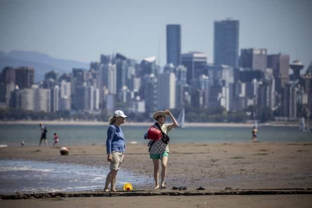 People are pictured at Vancouver's Spanish Banks on Friday. A heat wave shattered temperature records across the province over the weekend.  (Ben Nelms/CBC - image credit)