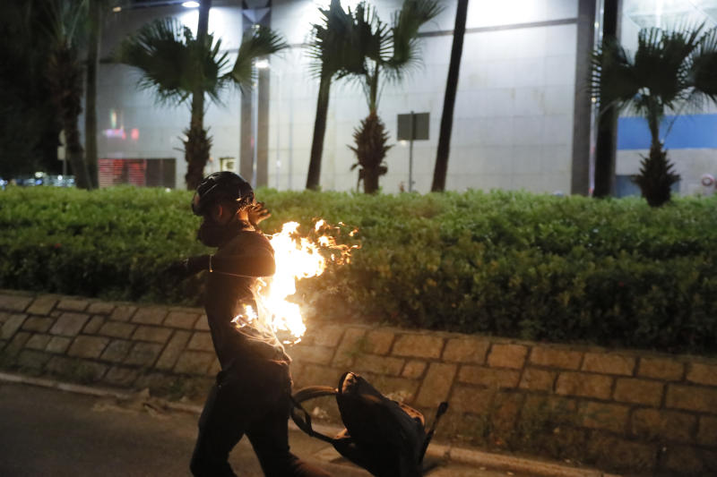 A protester's back catches fire after attempting to throw a Molotov cocktail during a protest in Hong Kong on Saturday, Sept. 21, 2019. Protesters in Hong Kong burned a Chinese flag and police fired pepper spray Saturday in renewed clashes over grievances by the anti-government demonstrators. (AP Photo/Kin Cheung)