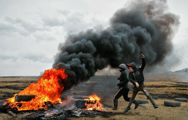 In this picture taken on Sunday, March 10, 2019, children jump after pushing a burning tire during a ritual marking the upcoming Clean Monday, the beginning of the Great Lent, 40 days ahead of Orthodox Easter, on the hills surrounding the village of Poplaca, in central Romania's Transylvania region. Romanian villagers burn piles of used tires then spin them in the Transylvanian hills in a ritual they believe will ward off evil spirits as they begin a period of 40 days of abstention, when Orthodox Christians cut out meat, fish, eggs, and dairy. (AP Photo/Vadim Ghirda)