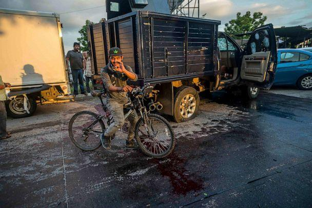 PHOTO: A man handles a bullet cartridge in a blooded street by a truck with a flat tire and covered with bullet hits after a gunfight in Culiacan, Mexico on Oct. 17, 2019. (Augusto Zurita/AP, FILE)
