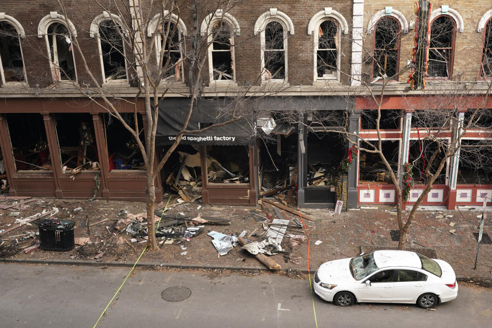 Debris remains on the sidewalk in front of buildings damaged in a Christmas Day explosion Tuesday, Dec. 29, 2020, in Nashville, Tenn. Officials have named 63-year-old Anthony Quinn Warner as the man behind the bombing in which he was killed, but the motive has remained elusive. (AP Photo/Mark Humphrey)