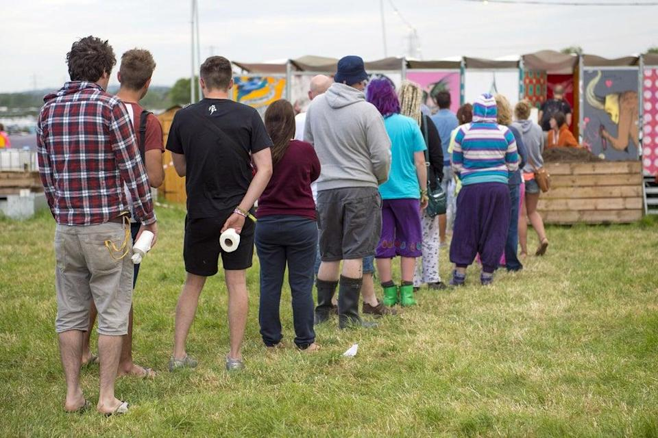Festival goers queue for the 'long drop' toilet facilities at the Glastonbury Festival, (PA)