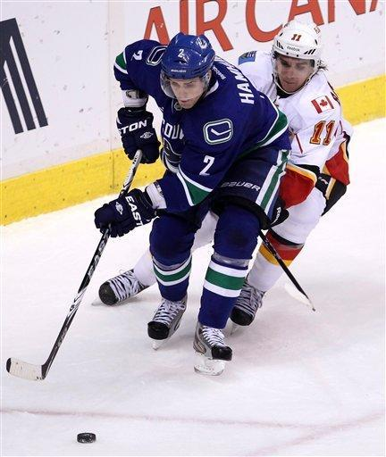 Vancouver Canucks defenseman Dan Hamhuis (2) and Calgary Flames center Mikael Backlund (11) fight for control of the puck during the second period of an NHL hockey game at Rogers Arena in Vancouver, British Columbia, Friday, Dec, 23, 2011. (AP Photo/The Canadian Press, Jonathan Hayward)