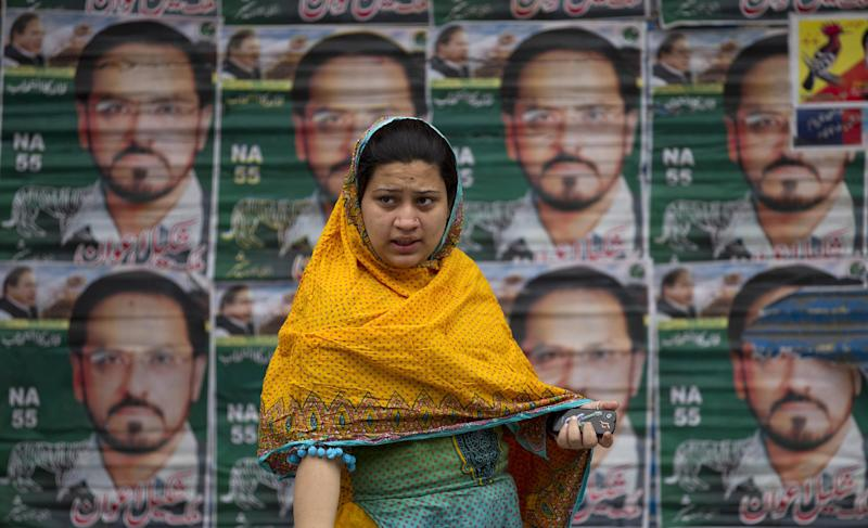 A Pakistani woman waits for transport after casting her ballot in Rawalpindi, Pakistan on Saturday, May 11, 2013. Defying the danger of militant attacks, Pakistanis streamed to the polls Saturday for a historic vote pitting a former cricket star against a two-time prime minister and an unpopular incumbent. But attacks that killed over a dozen people and wounded dozens more underlined the risks many people took just casting their ballots. (AP Photo/B.K. Bangash)