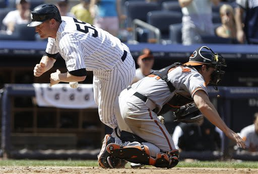 New York Yankees' Lyle Overbay (55) dives past Baltimore Orioles catcher Taylor Teagarden to score on a single by Eduardo Nunez during the sixth inning of a baseball game Saturday, July 6, 2013, in New York. (AP Photo/Frank Franklin II)