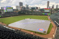 The Wrigley Field infield is covered with the rain tarp after the Chicago Cubs and Kansas City Royals head into a weather delay halfway through the seventh inning Saturday, Aug. 21, 2021, in Chicago. (AP Photo/Mark Black)
