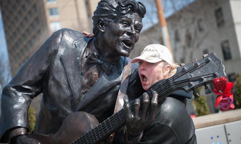 A woman with the statue of Chuck Berry in University City, Missouri.