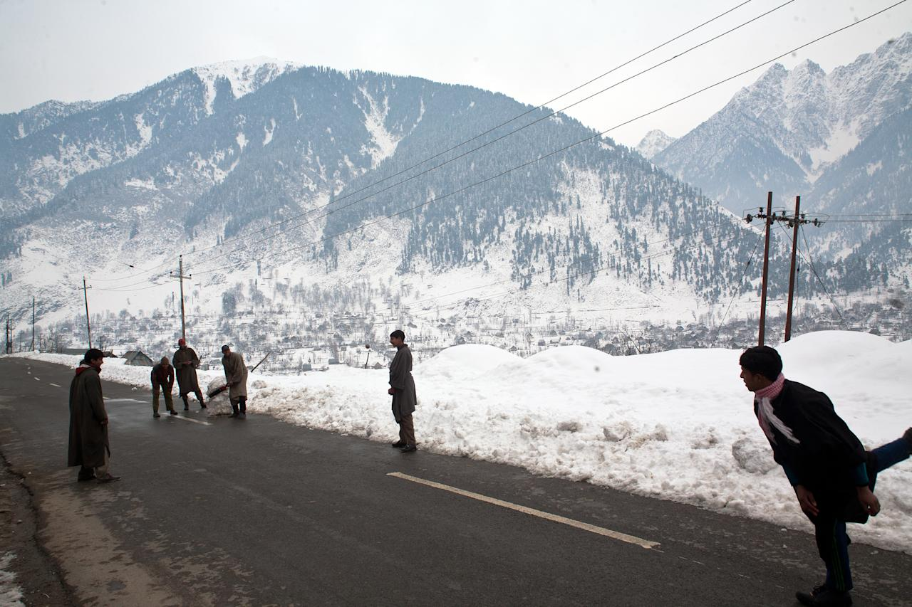 GUND, KASHMIR, INDIA - JANUARY 13: Children play cricket on a highway covered with snow in Gund 60 km (37 miles ) on January 13, 2014 east of Srinagar, the summer capital of Indian administered Kashmir, India. People got some respite from the cold as temperatures rose by several degrees in Kashmir valley  even as the weatherman has predicted light snowfall at isolated places in  the region Tuesday.  (Photo by Yawar Nazir/Getty Images)
