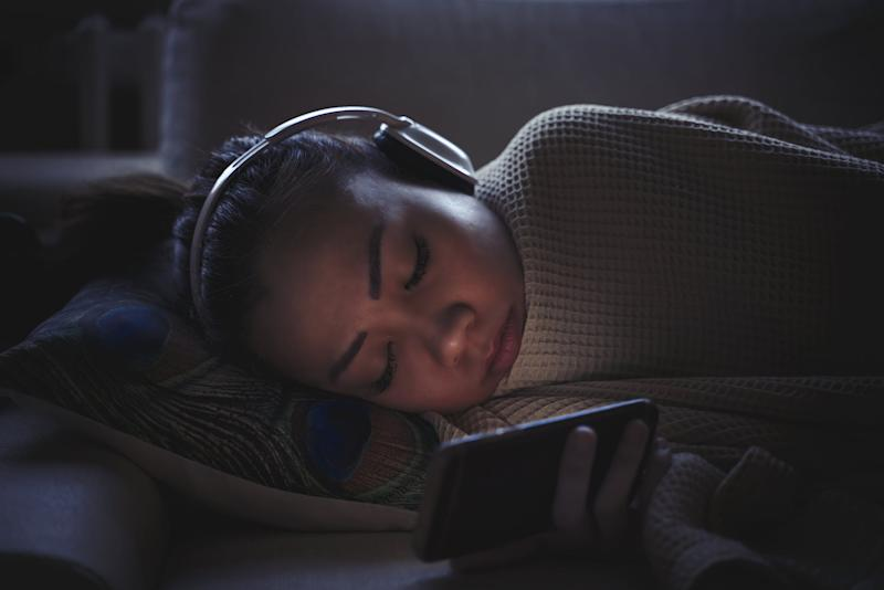 Woman fall a sleep while using mobile phone on couch with headphone
