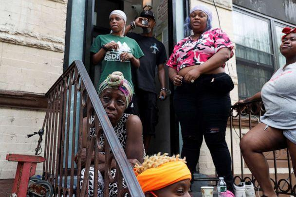 PHOTO: A woman grieves on the stoop of an apartment near the scene of the shooting where a 1-year-old boy was shot and killed in the Brooklyn borough of New York, July 13, 2020. (Shannon Stapleton/Reuters)