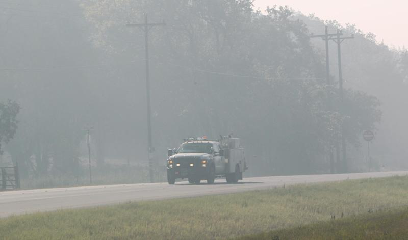 A truck drives through hanging smoke near Bastrop, Texas, Friday, Sept. 9, 2011.  Texas is suffering its worst wildfire outbreak in state history. The Bastrop-area fire has been the largest of nearly 190 wildfires the forest service says erupted this week, leaving nearly 1,700 homes statewide in charred ruins, killing four people and forcing thousands of people to evacuate.   (AP Photo/LM Otero)