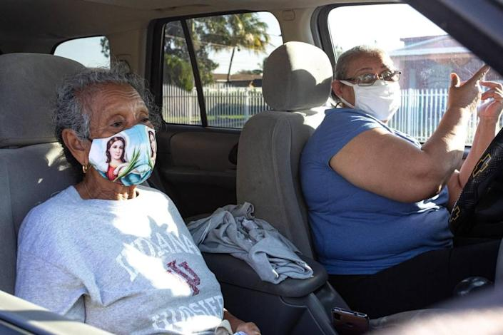 Gladis Mesino, 82, and Teresa Mesino, 68, wait in line inside a vehicle at the first walk-up mobile testing site open to Florida residents that won't require appointments at Miami Carol City Park in Miami Gardens, Florida, on Saturday, Feb. 20, 2021.