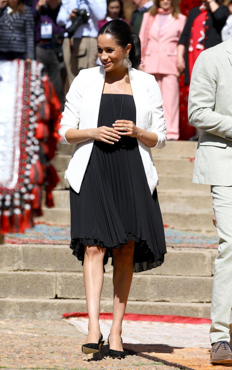 "<p>Meghan looked glamorous for a public walk through of the Andalusian Gardens in Rabat wearing a black pleated dress, white blazer from Aritzia, large <a href=""https://www.neimanmarcus.com/p/gas-bijoux-onde-drop-earrings-prod220120063"" rel=""nofollow noopener"" target=""_blank"" data-ylk=""slk:gold statement earrings by Gas Bijoux"" class=""link rapid-noclick-resp"">gold statement earrings by Gas Bijoux </a>and black Manolo Blahnik sling back heels. </p><p><a class=""link rapid-noclick-resp"" href=""https://go.redirectingat.com?id=74968X1596630&url=https%3A%2F%2Fwww.saksfifthavenue.com%2Fmanolo-blahnik-carolyne-suede-slingbacks%2Fproduct%2F0400088941109&sref=https%3A%2F%2Fwww.townandcountrymag.com%2Fstyle%2Ffashion-trends%2Fg3272%2Fmeghan-markle-preppy-style%2F"" rel=""nofollow noopener"" target=""_blank"" data-ylk=""slk:Shop Now"">Shop Now</a> <em>Carolyne Suede Slingbacks, Manolo Blahnik, $645</em></p><p><a class=""link rapid-noclick-resp"" href=""https://www.neimanmarcus.com/p/gas-bijoux-onde-drop-earrings-prod220120063"" rel=""nofollow noopener"" target=""_blank"" data-ylk=""slk:Shop Now"">Shop Now</a> <em>Onde Drop Earrings, Gas Bijoux, $200</em></p>"