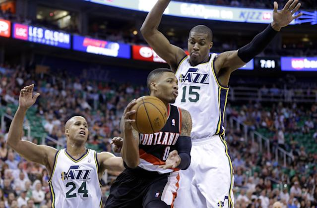 Portland Trail Blazers' Damian Lillard (0) passes the ball as Utah Jazz's Richard Jefferson (24) and Derrick Favors (15) defend in the second quarter during an NBA basketball game on Friday, April 11, 2014, in Salt Lake City. (AP Photo/Rick Bowmer)