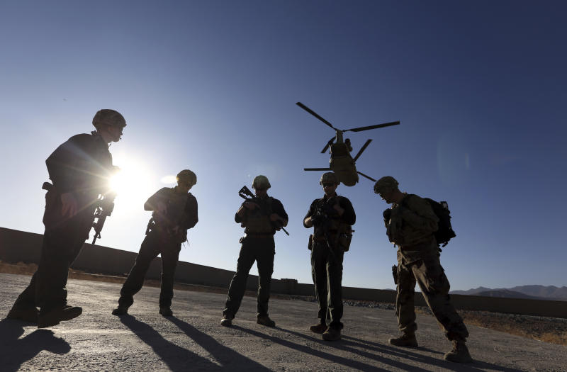 FILE - In this Nov. 30, 2017 file photo, American soldiers wait on the tarmac in Logar province, Afghanistan. Top officials in the White House were aware in early 2019 of classified intelligence indicating Russia was secretly offering bounties to the Taliban for the deaths of Americans, a full year earlier than has been previously reported.  (AP Photo/Rahmat Gul, File)