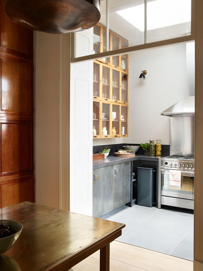 In the kitchen, traditional elements mix with the super modern. The wall cabinets are originally from the British Museum, while the base units were made by Fisher and fitted with Irish fossil countertops. The bins were custom-made for the space.