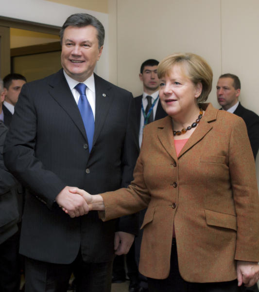 German Chancellor Angela Merkel, right, and Ukrainian President Viktor Yanukovych meet in a hotel in Vilnius, Lithuania, Friday, Nov. 29, 2013. The European Union extended its geopolitical reach eastward on Friday by sealing association agreements with Georgia and Moldova, but blamed Russia for missing out on a landmark deal with Ukraine. (AP Photo/Mykhailo Markiv)