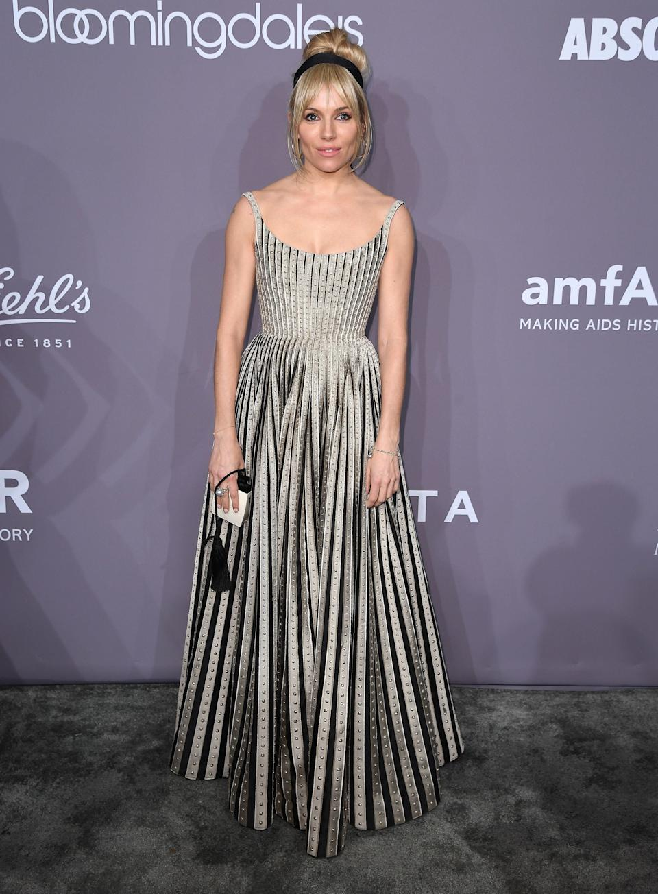 <p>Sienna stayed true to her boho chic style in a striped Dior gown paired with a hairband and updo. <em>[Photo: Getty]</em> </p>
