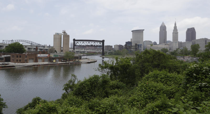 "The Cuyahoga River winds it way toward Cleveland, Tuesday, May 28, 2019. Fifty years after the Cuyahoga River's famous fire, a plucky new generation of Cleveland artists and entrepreneurs has turned the old jokes about the ""mistake on the lake"" into inspiration and forged the decades of embarrassment into a fiery brand of local pride. (AP Photo/Tony Dejak)"