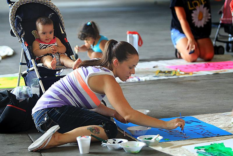 In this Saturday, July 28, 2012 photo, Luis Rodriguez watches his mother,Theresa, paint signs to welcome home her husband during a banner-making party at a hangar at New River Air Station near Camp Lejeune in Jacksonville, N.C. Families and friends will hang large sheets and banners on a fence outside the base to welcome home Marines from Afghanistan and Iraq, and wave posterboard signs as they wait for their arrival. (AP Photo/Chuck Beckley)