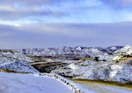 <p>In this photo, you can see a valley in the Badlands covered in a dusting of snow. The snow makes the space look so different. </p>