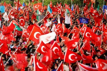 People wave Turkey's national flags as they attend a ceremony marking the first anniversary of the attempted coup in front of the Turkish Parliament in Ankara, Turkey July 16, 2017. REUTERS/Umit Bektas