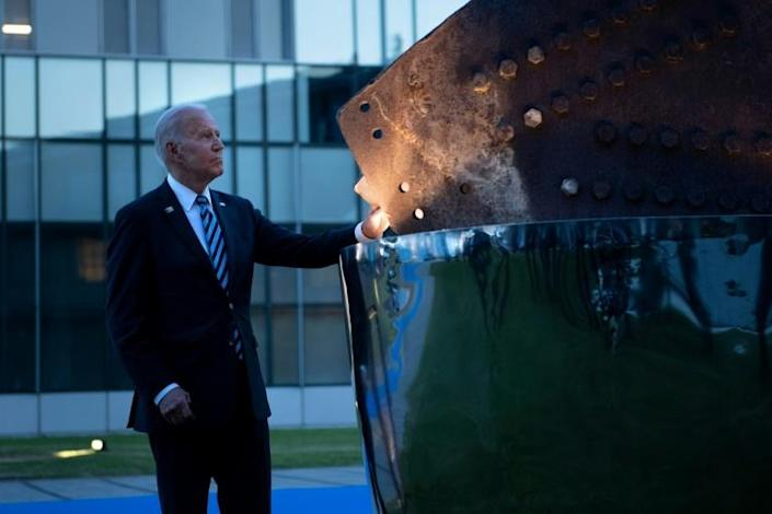 US President Joe Biden touches a September 11 memorial at the NATO headquarters in Brussels