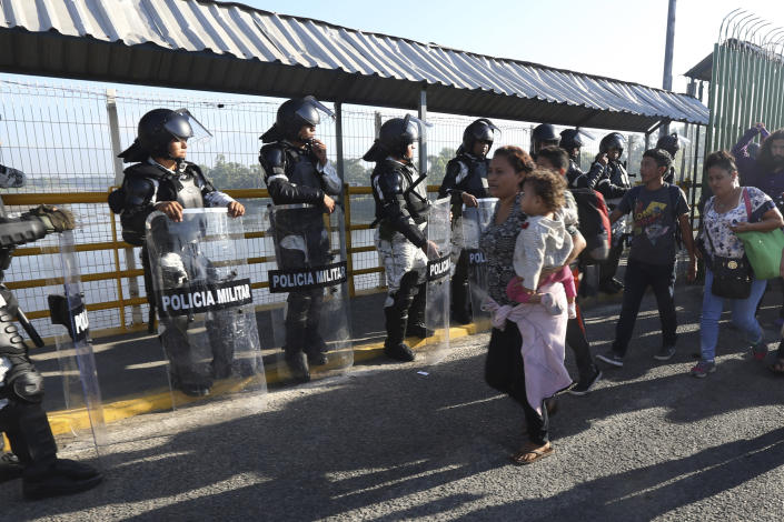 Honduran migrants cross the border into Mexico in Ciudad Hidalgo, Mexico, Saturday, Jan. 18, 2020. More than a thousand Central American migrants surged onto the bridge spanning the Suchiate River, that marks the border with Guatemala. (AP Photo/Marco Ugarte)