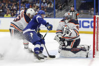 Tampa Bay Lightning's Yanni Gourde crashes the net for a rebound against Edmonton Oilers goaltender Mike Smith as Matt Benning defends during the second period of an NHL hockey game Thursday, Feb. 13, 2020, in Tampa, Fla. (AP Photo/Mike Carlson)