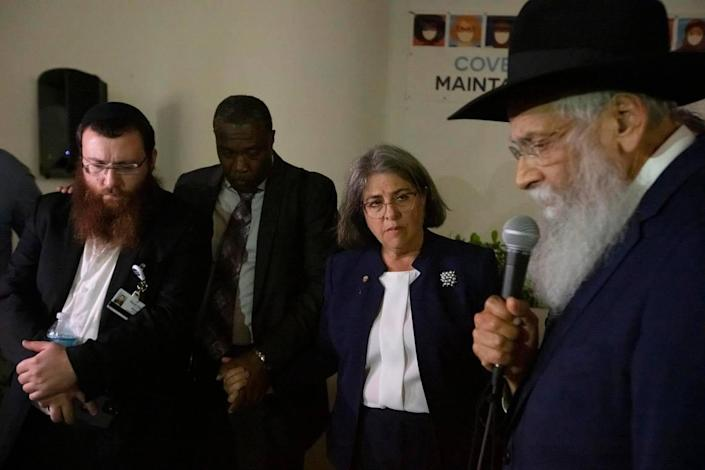 Rabbi Sholom Lipskar, spiritual leader of the Shul of Bal Harbour, prays during the search-and-rescue operation after the partial collapse of the Champlain Towers South in Surfside on Thursday night June 24th., 2021. At left are Rabbi Mendy Levy, Chabad Chaplaincy Network Chaplain -- Mount Sinai Medical Center and Miami-Dade Mayor Daniella Levine Cava.