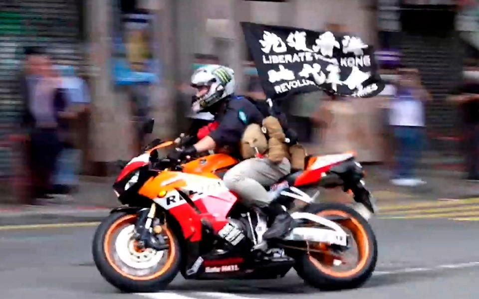 """Tong Ying-kit on a motorcycle while carrying a flag reading """"Liberate Hong Kong, Revolution of our times"""" during a protest in Hong Kong on July 1, 2020 - Cable TV Hong Kong"""
