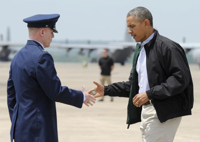 President Barack Obama shakes hands with Col. Patrick Rhatigan, Commander, 19th Airlift Wing & Little Rock AFB, left, and give him a challenge coin after Obama arrives at Little Rock Air Force Base, Ark., Wednesday, May 7, 2014. Obama is visiting with first responders and families affected by the recent tornados. (AP Photo/Susan Walsh)