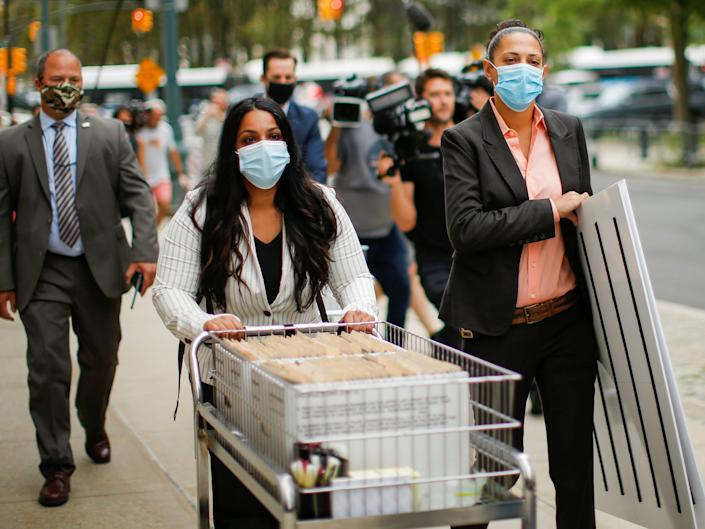 Prosecutors wearing facemasks push a cart with white cardboard boxes of evidence along a sidewalk