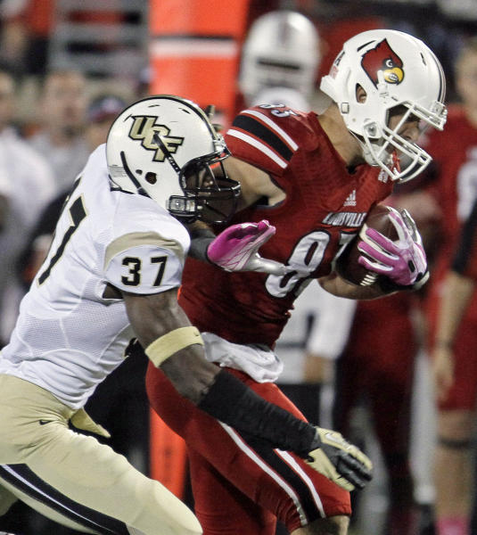 Louisville tight end Ryan Hubbell (83) gets caught from behind by Central Florida's Brandon Alexander (37) after a 34-yard reception in the first quarter of an NCAA college football game in Louisville, Ky., Friday, Oct. 18, 2013. (AP Photo/Garry Jones)