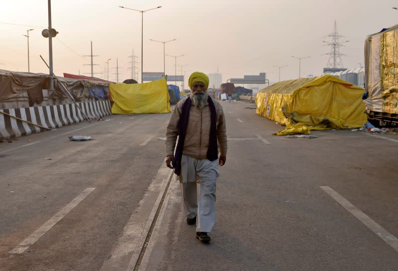 A farmer walks at a site where farmers have gathered to protest against farm laws at Ghaziabad