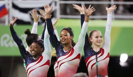 Simone Biles (L), Gabrielle Douglas (C), Madison Kocian (R), Alexandra Raisman (back) and Laurie Hernandez (back) celebrate winning the gold in the women's team final. REUTERS/Damir Sagolj
