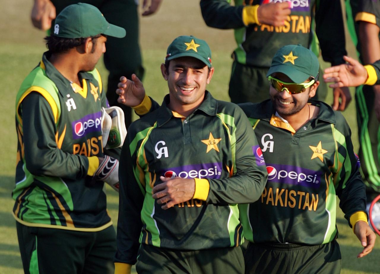 Pakistan players Saeed Ajmal and Ahmed Shehzad are happy with victory during the 2nd game of the three match ODI cricket series between Pakistan and hosts Zimbabwe at the Harare Sports Club on August 29, 2013. AFP PHOTO / JEKESAI NJIKIZANA        (Photo credit should read JEKESAI NJIKIZANA/AFP/Getty Images)