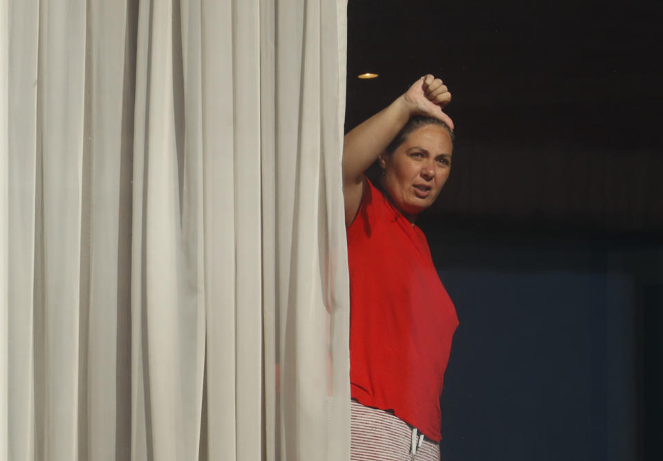 "<p>A woman gestures towards the media from her room at the Radisson Blu Edwardian Hotel, near Heathrow Airport, London, Monday Feb. 15, 2021. Passengers from Heathrow airport they will remain at the hotel during a 10 day quarantine period after returning to England from one of 33 ""red list"" countries. New regulations now in force require anyone who has been in a 'high-risk' location to enter England through a designated port and have pre-booked a package to stay at one of the Government's managed quarantine facilities. (AP Photo/Alastair Grant)</p>"