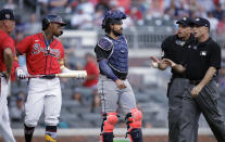 Umpires speak with Atlanta Braves' Ronald Acuna Jr., holding bat, and manager Brian Snitker, left, as Miami Marlins catcher Jorge Alfaro, center, looks on after Acuna was hit by the first pitch thrown by Marlins' Pablo Lopez in the first inning of a baseball game Friday, July 2, 2021, in Atlanta. (AP Photo/Ben Margot)