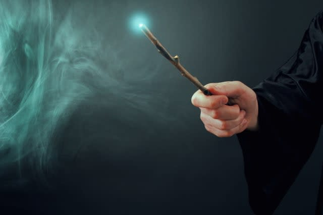 A fantasy wizard making magic with wand.