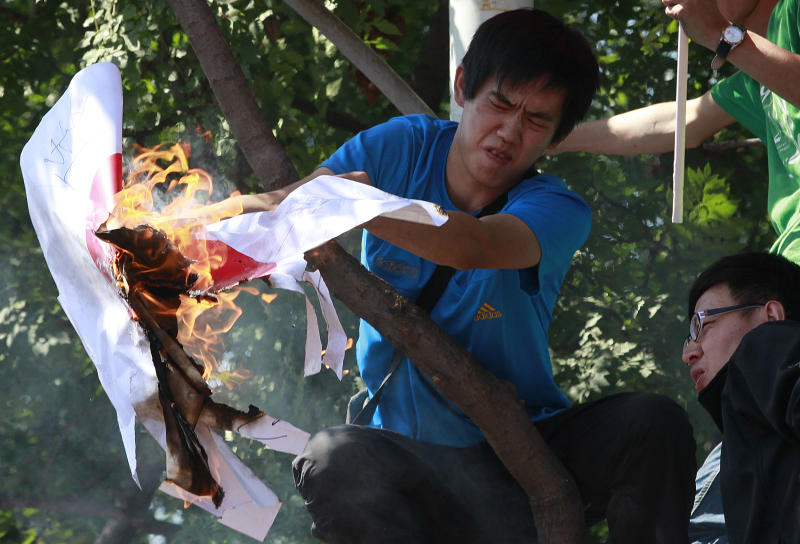 Chinese protesters burn a Japanese flag outside the Japanese embassy in Beijing, China, Saturday, Sept. 15, 2012. Tensions between the two countries flared anew after the Japanese government bought the disputed islands from their private Japanese owners this week. The uninhabited islands, Senkaku in Japan and Diaoyu in China, claimed by both countries as well as Taiwan, have become a rallying point for nationalists on both sides. (AP Photo/Ng Han Guan)