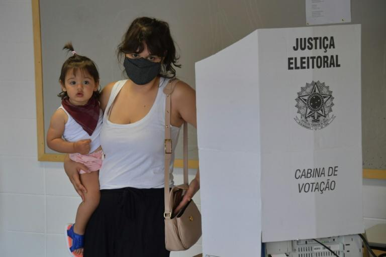 A woman carrying a child votes at a polling station in Sao Paulo during Brazil's municipal elections on November 15, 2020