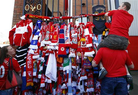 Men put a scarf on the Shankly gates before a memorial service to mark the 25th anniversary of the Hillsborough disaster at Anfield in Liverpool, northern England April 15, 2014. REUTERS/Darren Staples